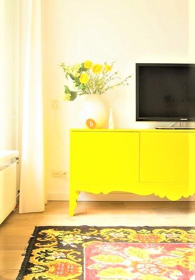 mobile tv giallo con vaso bianco con fiorellini
