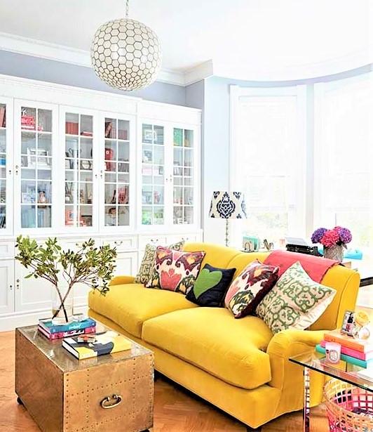 Salotto con divano giallo e cuscini colorati