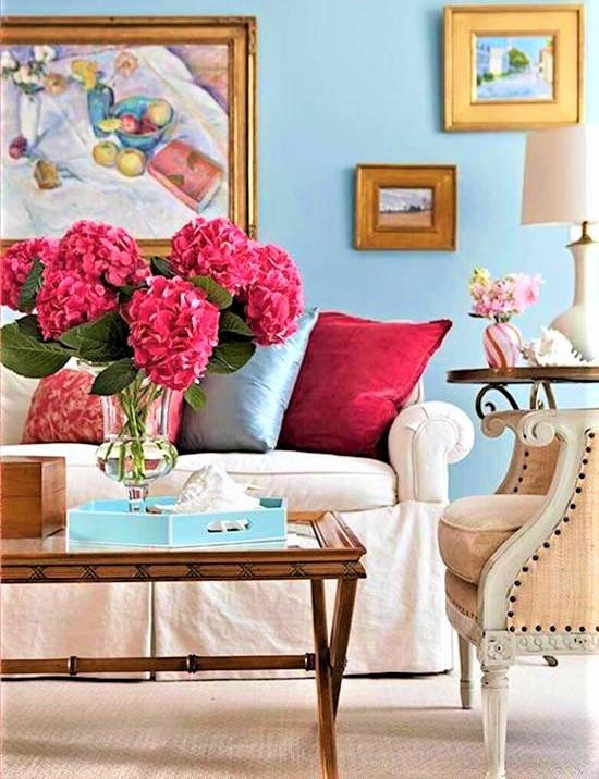 divano bianco con cuscini colorati e vaso di ortensie