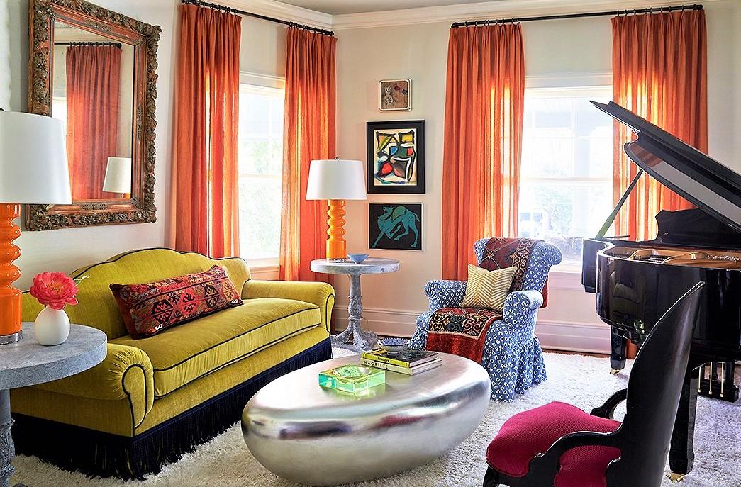 salotto con divano giallo e tende arancioni