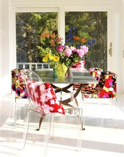 sala da pranzo con sedie in plexigas e fiori