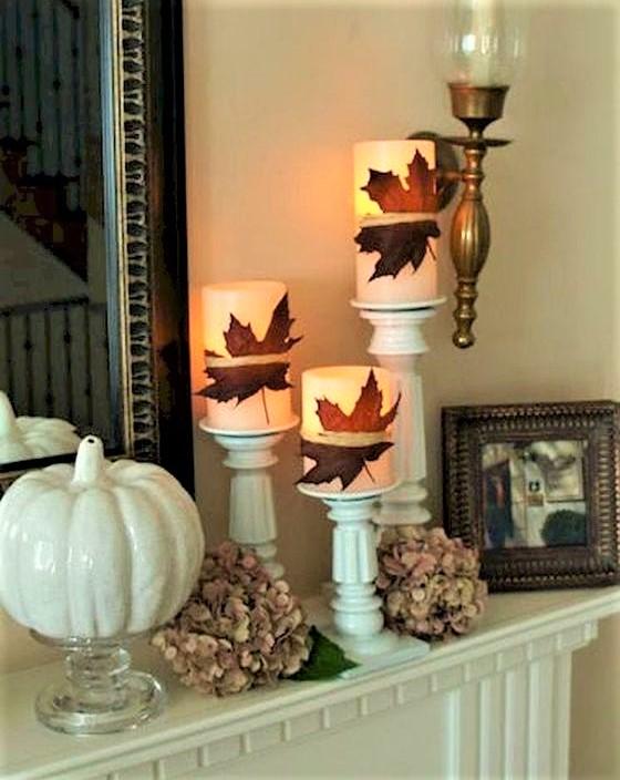 candele bianche con foglie secche e zucca bianca