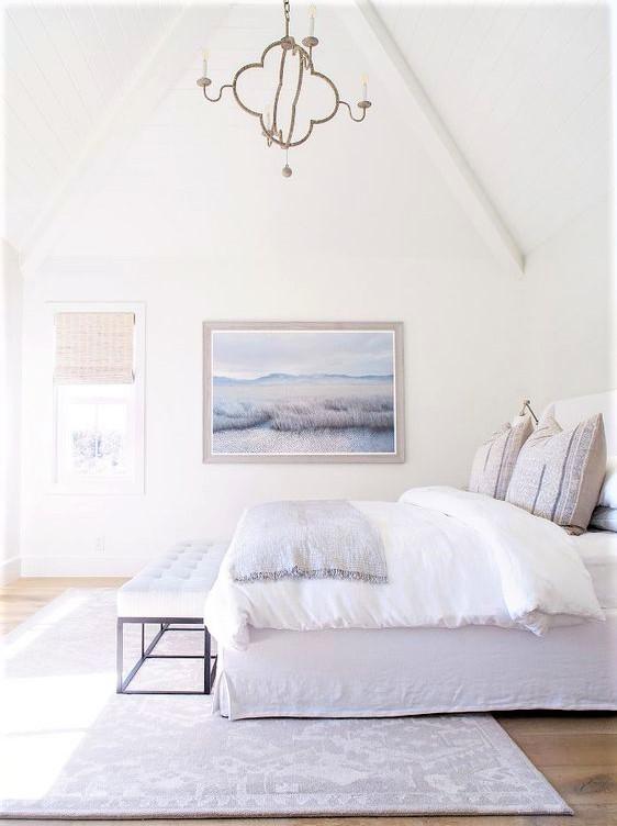 camera da letto con letto bianco e quadro blu