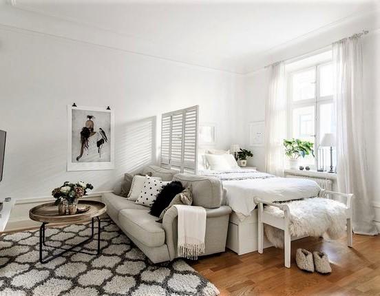 grande tappeto con rombi, divano biege e grande finestra