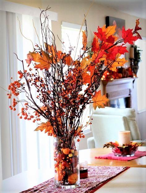 vaso in vetro con rametti e foglie arancioni