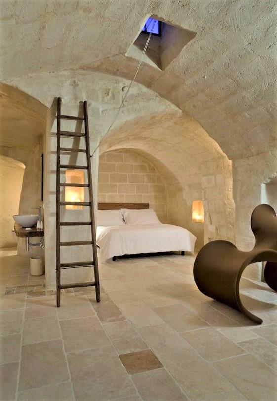 scale in legno e letto con lenzuola bianche